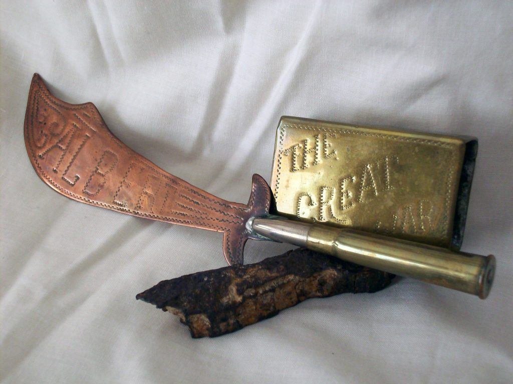 "Two pieces of trench art (the matchbox cover engraved ""The Great War""; the paper- knife engraved ""Albert"", and ""Ancre"" on the reverse; the handle is a spent .303 cartridge, for a Lee Enfield rifle or a Lewis machine-gun); and a piece of shrapnel preserved by ALL (exact origin not known but possibly related to the July 26 diary entry)."